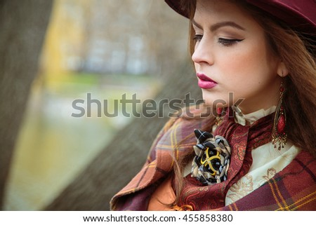Young beautiful thoughtful girl in an ancient dress and maroon hat standing in park. Retro style. Parks, outdoors
