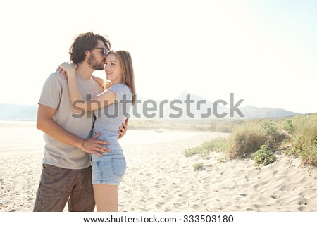Young beautiful tourist couple enjoying a summer holiday on a destination coast on a sunny vacation, hugging and kissing with happy expressions, sandy beach outdoors. Travel and honeymoon lifestyle. - stock photo