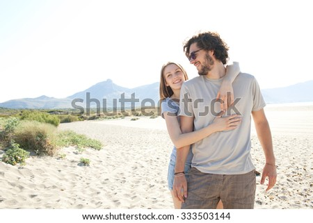 Young beautiful tourist couple enjoying a summer holiday on destination coast on a sunny vacation, with girl hugging man with joyful expressions, sandy beach outdoors. Travel and honeymoon lifestyle. - stock photo