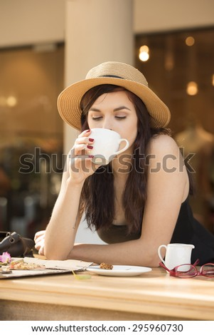 young beautiful traveler enjoying a coffee at street cafe - stock photo