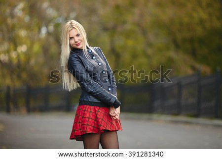 Young beautiful trendy dressed blonde woman posing outdoors against blurry foliage background smiling looking into camera - stock photo