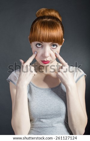 Young beautiful unhappy stressed overworked woman with red lips has tired eyes on black background. Negative facial - stock photo