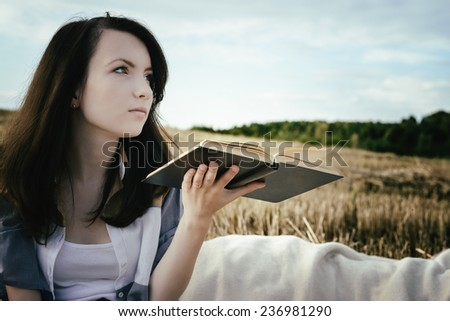 young beautiful unusual girl illustrates conceptual idea with book - stock photo