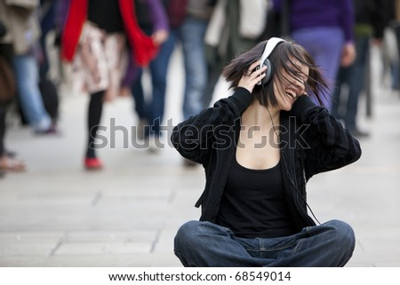 Young beautiful urban girl singing among the crowd. - stock photo
