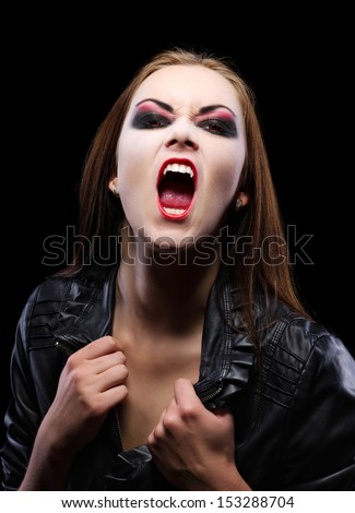 Young beautiful vampire woman on black - stock photo