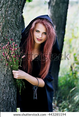 young beautiful witch gathers herbs for potions