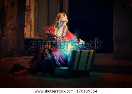 Young beautiful witch in a dark room conjuring a spell - stock photo