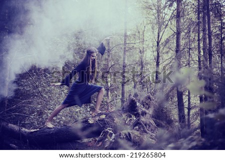 young beautiful witch in autumn forest - stock photo
