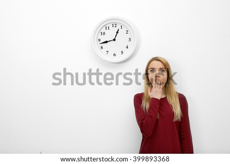 Young beautiful woman and clock on wall