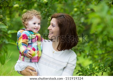 Young beautiful woman and her baby daughter walking in an apple garden in autumn - stock photo