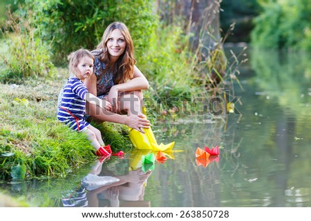 Young beautiful woman and her little kid daughter playing together with paper boats in a river. Creative leisure with kids. - stock photo