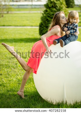 Young beautiful woman and small boy on big white ball lamp on green grass