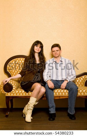 young beautiful woman and young man sitting on sofa in room - stock photo