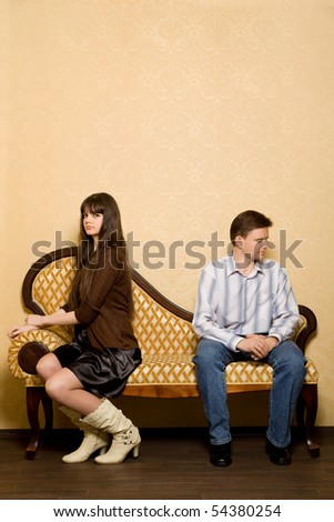young beautiful woman and young man sitting on sofa in room, have taken offence against each other - stock photo