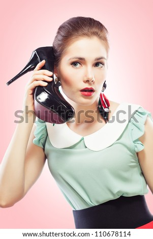 Young beautiful woman answering a shoe telephone holding it near her face and talking, pink background. Pin-up style. - stock photo