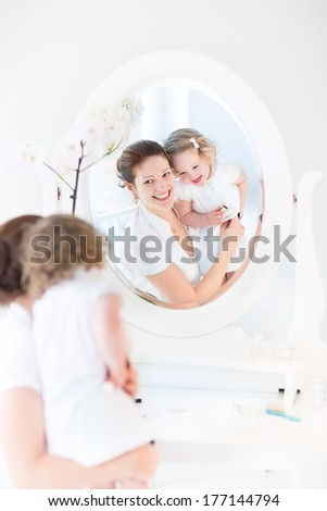 Young beautiful woman applying make up and cosmetics with a brush sitting in front of a round mirror in a white sunny bedroom and her little toddler daughter watching her with big interest - stock photo