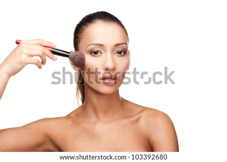 Young beautiful woman applying makeup isolated on white - stock photo