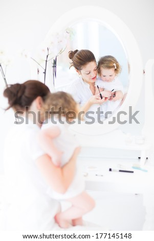 Young beautiful woman applying mascara and other make up in front of a round mirror in a white sunny bedroom and her little toddler daughter watching her with big interest - stock photo