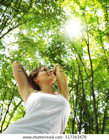 Young beautiful woman arms raised enjoying the nature in green forest