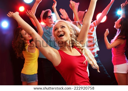 Young beautiful woman at a party with friends - stock photo