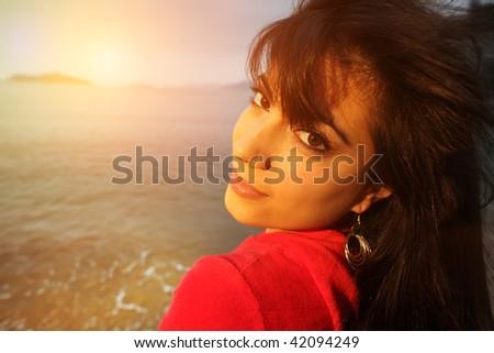 Young beautiful woman at beach at sunset looking back at camera. - stock photo