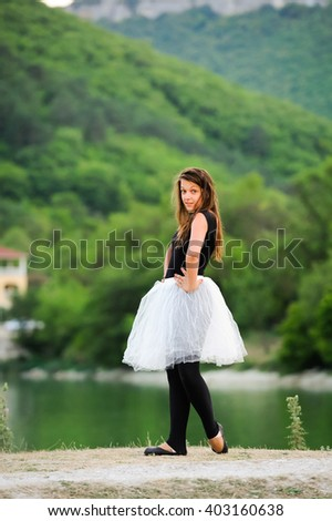 Young beautiful woman, ballerina dancer in black pointe shoes and skirt tutu on green nature near the lake. Cute girl with long hair posing outdoor. Sporty gymnast girl doing exercise in nature. - stock photo