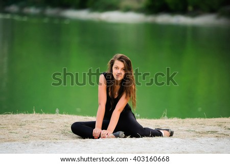 Young beautiful woman, ballerina dancer in black pointe shoes on green nature background near the lake. Cute girl with long hair posing outdoor. Sporty gymnast girl doing exercise in nature. - stock photo