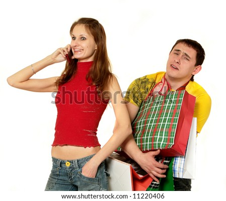 Young beautiful woman being on the phone and handsome man with bags do shopping