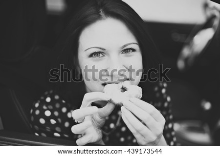 Young beautiful woman bites off the donut in the car, look into the camera, close-up, black-and-white image. - stock photo