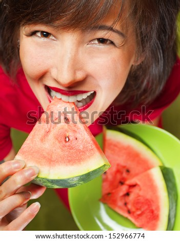Young beautiful woman biting slice of watermelon, top view