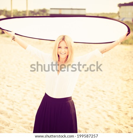 young beautiful woman blonde poses on a beach. dressed in a white shirt and a black skirt. fashion model. Photo with instagram style filters