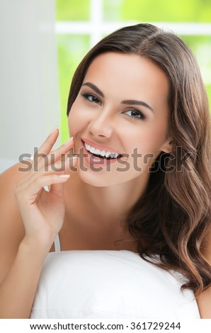 Young beautiful woman brunette waking up with pillow, at bedroom - stock photo