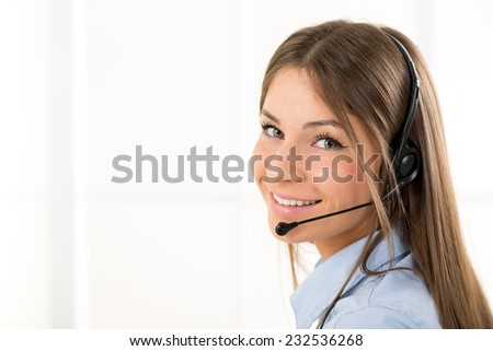 Young beautiful woman, call operator with headset smiling looking at the camera. - stock photo