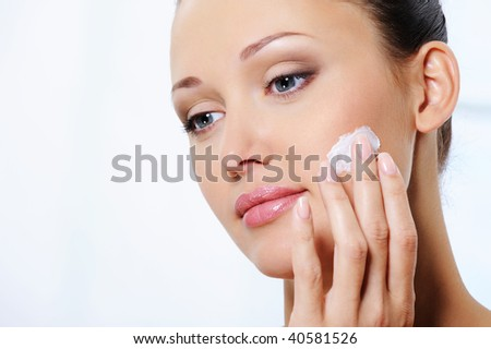 Young beautiful woman caring of her face with moisturizer cream - stock photo