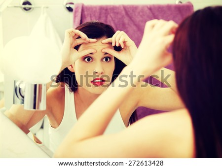 Young beautiful woman checking her wrinkles - stock photo