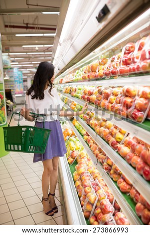 Young beautiful woman choosing apples at the supermarket