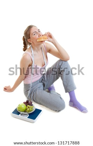 young beautiful woman choosing between burger and fruits - stock photo