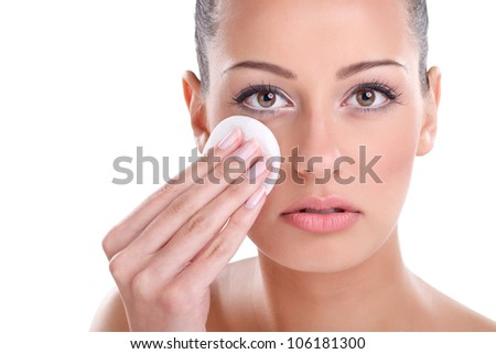 young beautiful woman cleaning face with cotton pad - stock photo