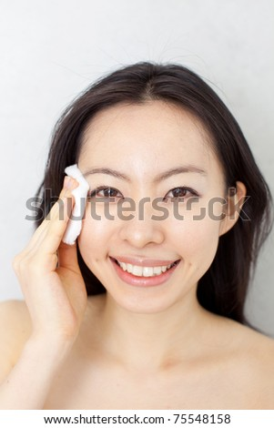 young beautiful woman cleaning her face with cotton - stock photo