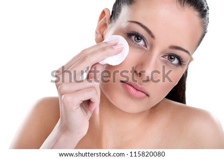 Young Beautiful woman cleaning skin on face with cotton pad - stock photo