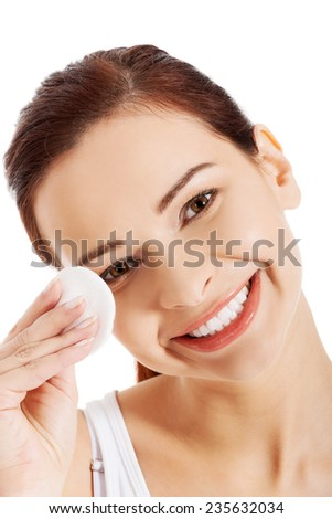 Young beautiful woman cleans the eye make-up. - stock photo