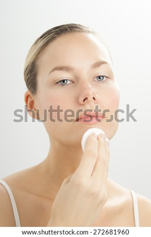 Young beautiful woman cleansing face with toner on cotton disk. Makeup removal in skincare routine. - stock photo