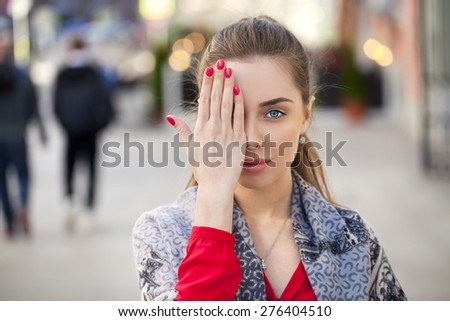 Young beautiful woman closes her eyes with his hand on a background of the street - stock photo
