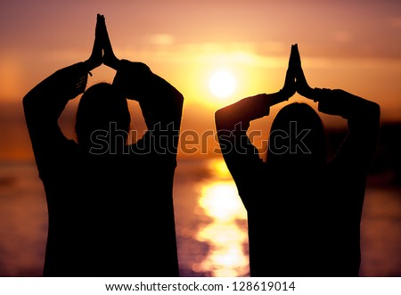 Young beautiful woman couple making yoga on sunset - stock photo