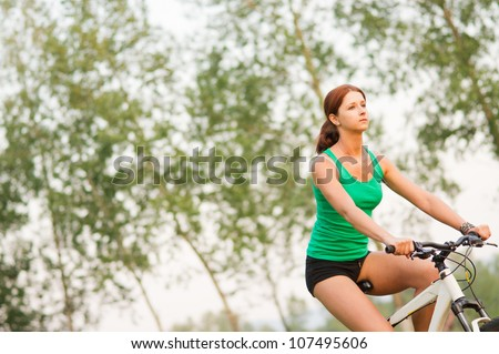 Young beautiful woman cycling in the park