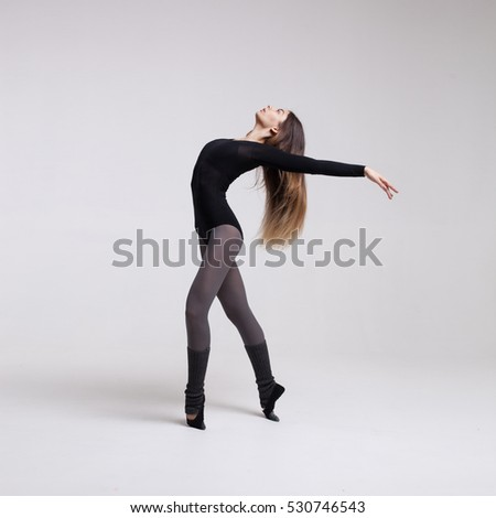 young beautiful woman dancer with long brown hair wearing black swimsuit posing on a light grey studio background