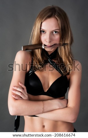 Young beautiful woman defending with bellicose knife in teeth over grey background - stock photo
