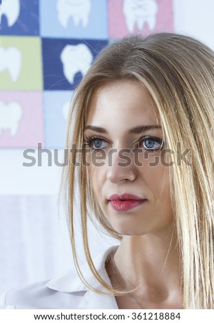 Young beautiful woman dentist portrait. against the background of the teeth - stock photo