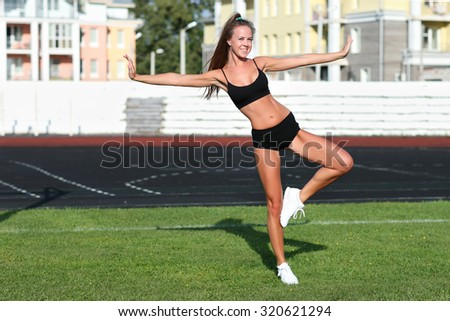 Young beautiful woman doing core workout at a stadium