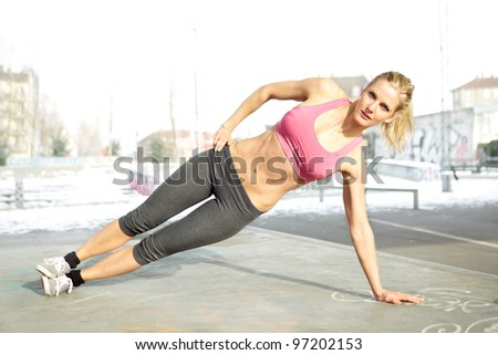 Young beautiful woman doing core workout outside